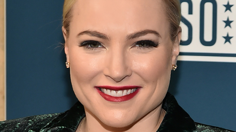 Meghan McCain wears red lipstick and smiles.
