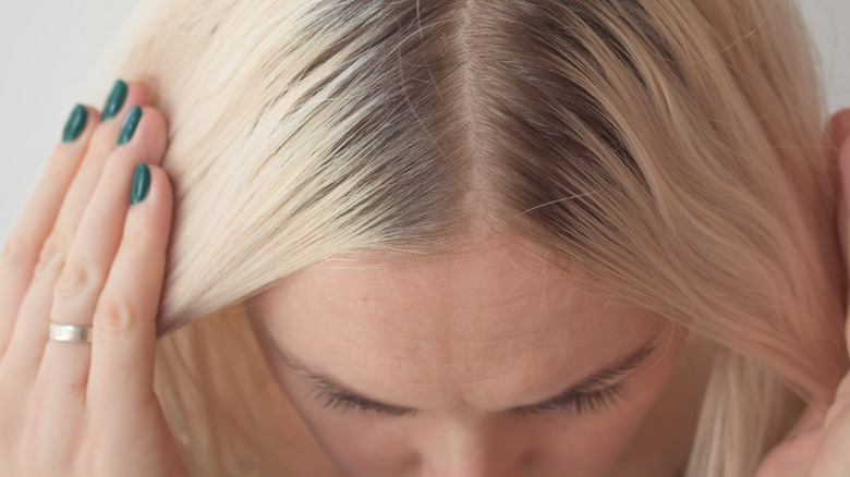 Blonde haired woman parting her hair