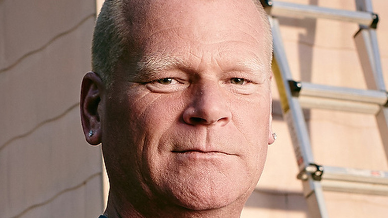 Mike Holmes standing in front of a house