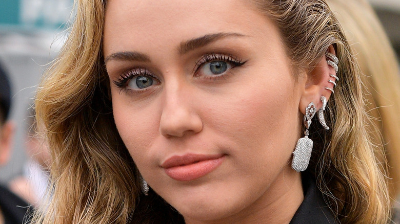 Miley Cyrus with slight grin and multiple earrings