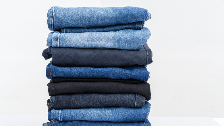 Stacked jeans against white background