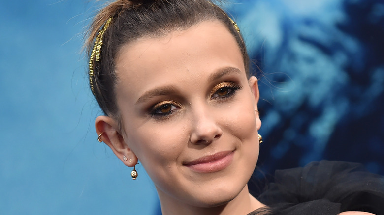 Millie Bobby Brown looking to the side with slight smirk