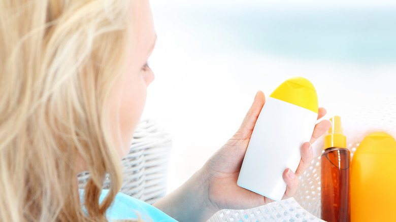 Blonde woman looking at sunscreen she's holding.