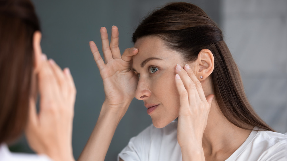 Woman inspecting skin in mirror