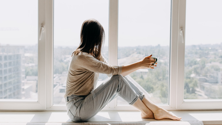 Woman holding a mug looking out a window