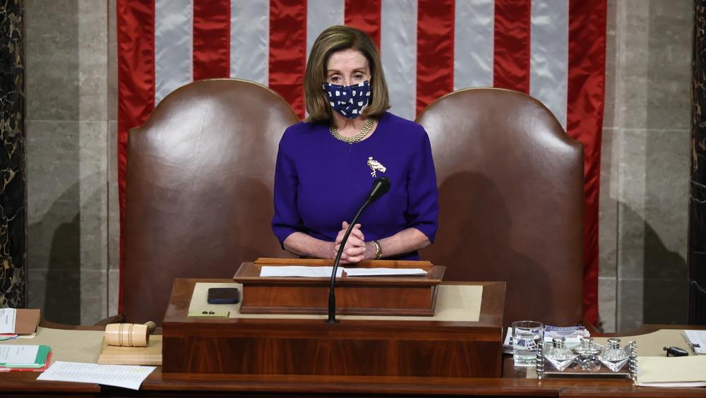 Nancy Pelosi at lectern, wearing blue mask