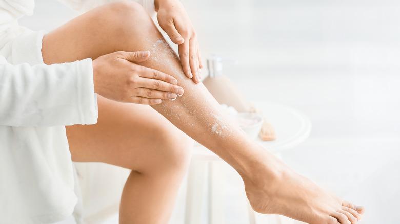 A woman scrubs her leg