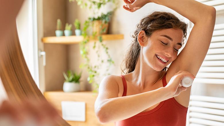 Woman applying deodorant bar to skin