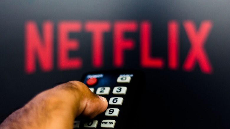 hand with remote selecting netflix