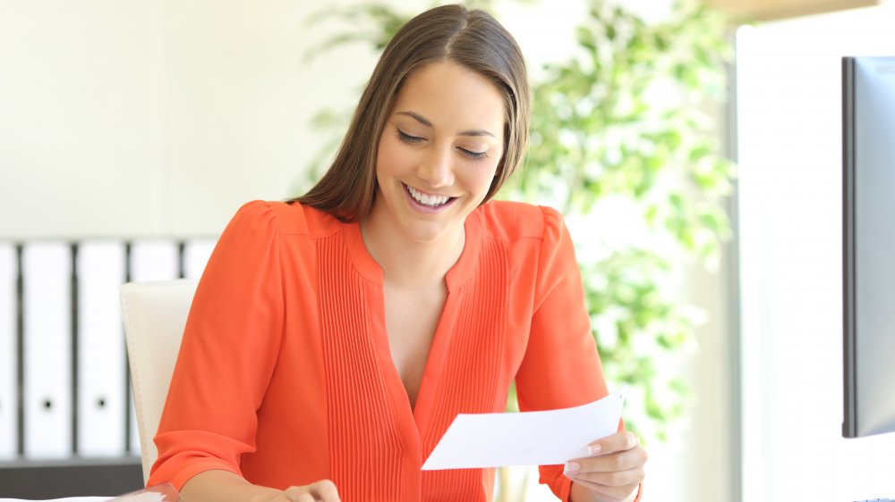 Woman smiling in an orange blouse in an office