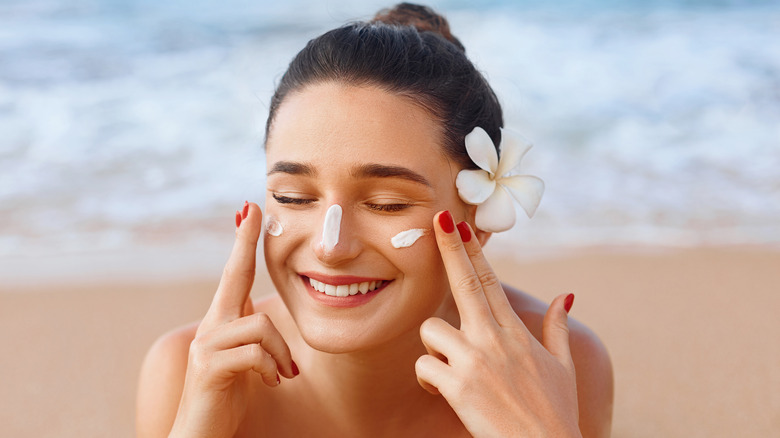 Woman applying sunscreen to her face