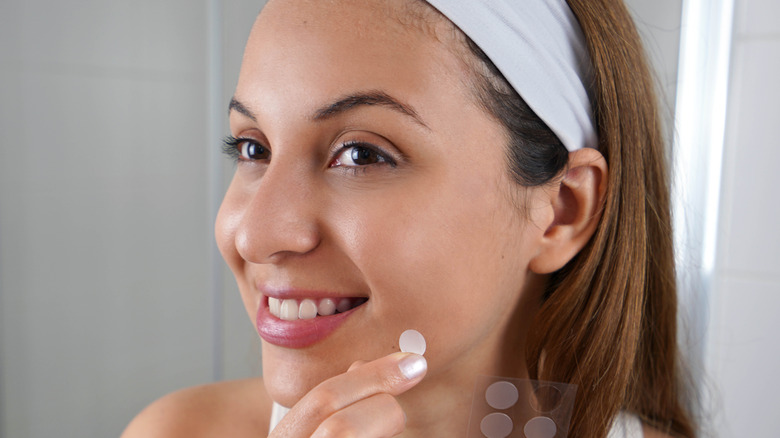 Woman applying pimple patch