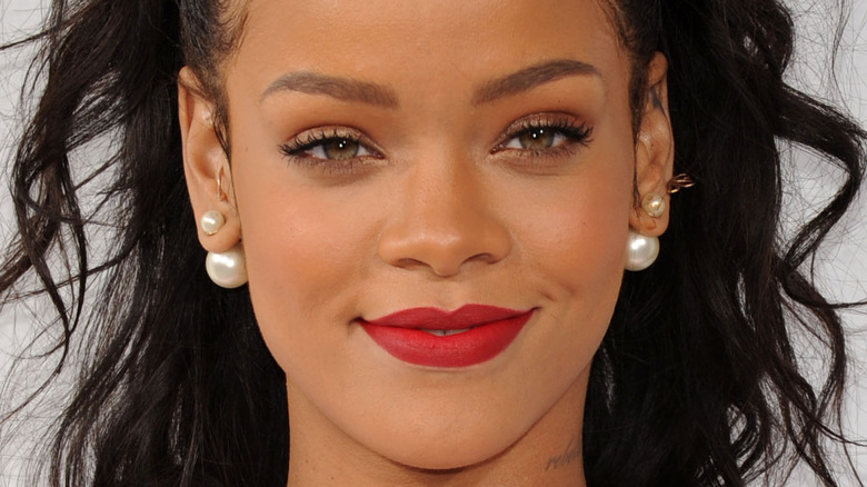 Rihanna, fashion icon, grinning at an event