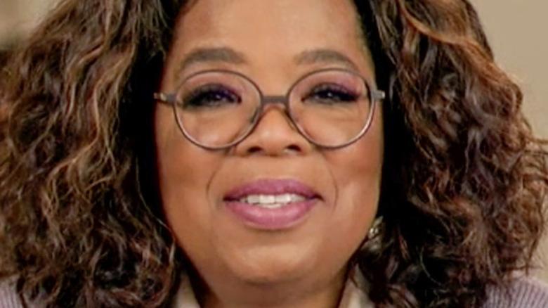 Oprah smiling, wearing glasses