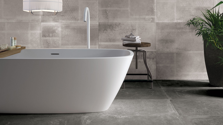 Bathtub situated in grey bathroom