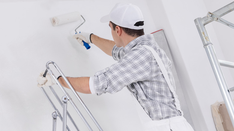 Man standing on a ladder with a paint roller in his hand.