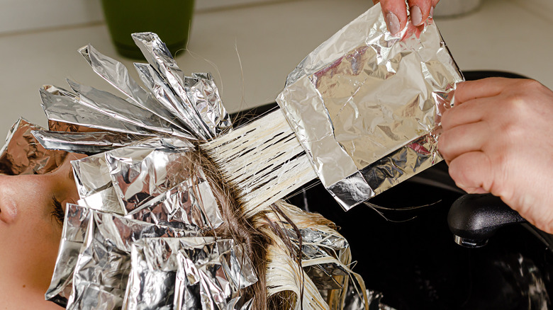 Stylist removing foils from an all-over highlight.