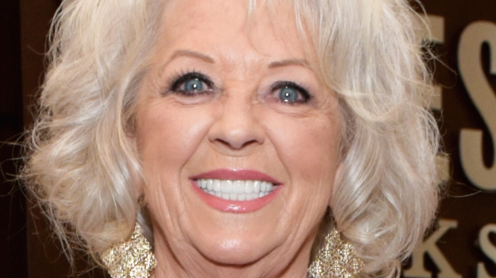 Paula Deen smiles with large gold earrings.