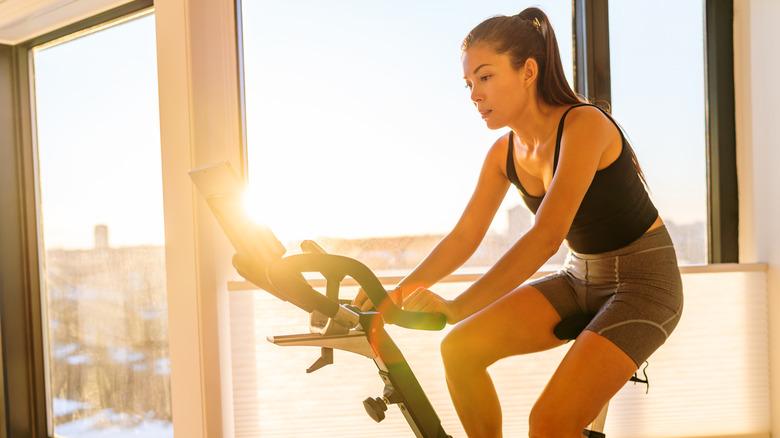 Woman rides an indoor workout bike