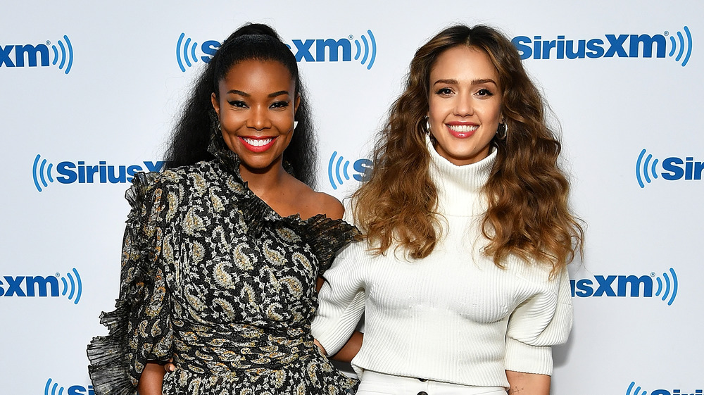 Gabrielle Union in black outfit smiling with Jessica Alba in white outfit