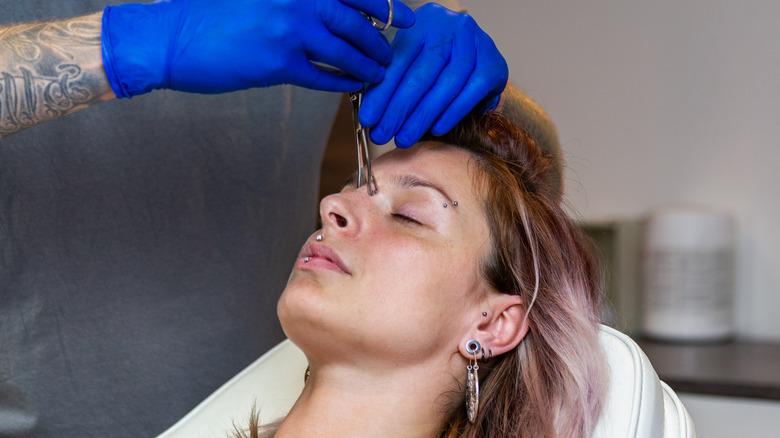 Woman getting pierced