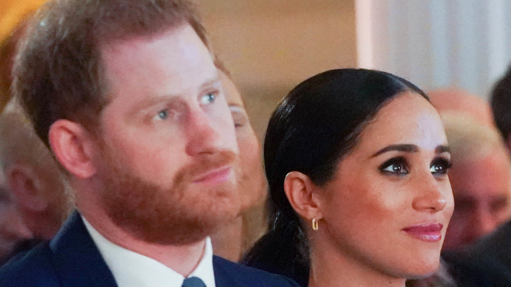 Prince Harry and Meghan Markle looking serious