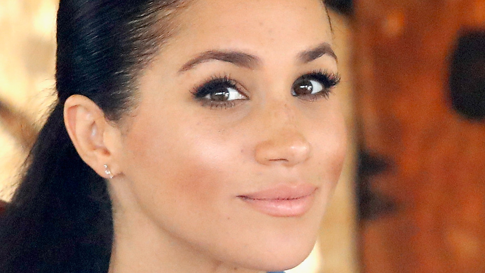 Meghan Markle grinning with hair pulled back