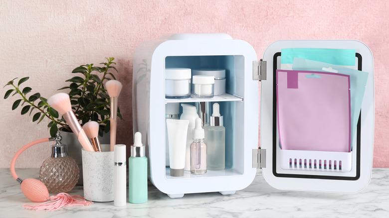 Beauty fridge next to makeup brushes and perfume bottle