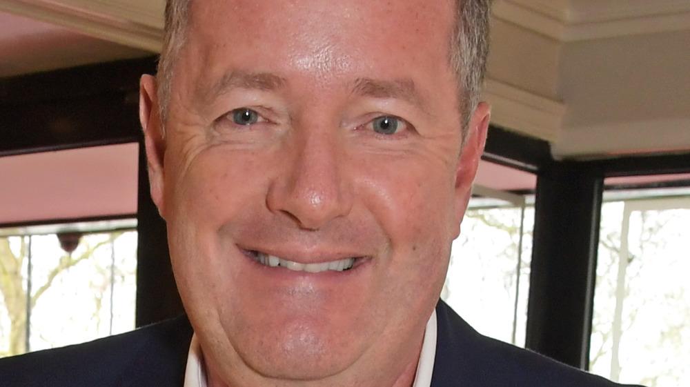 Piers Morgan in front of window