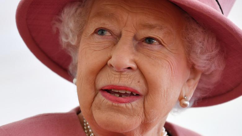 Queen Elizabeth wears a pink suit and hat