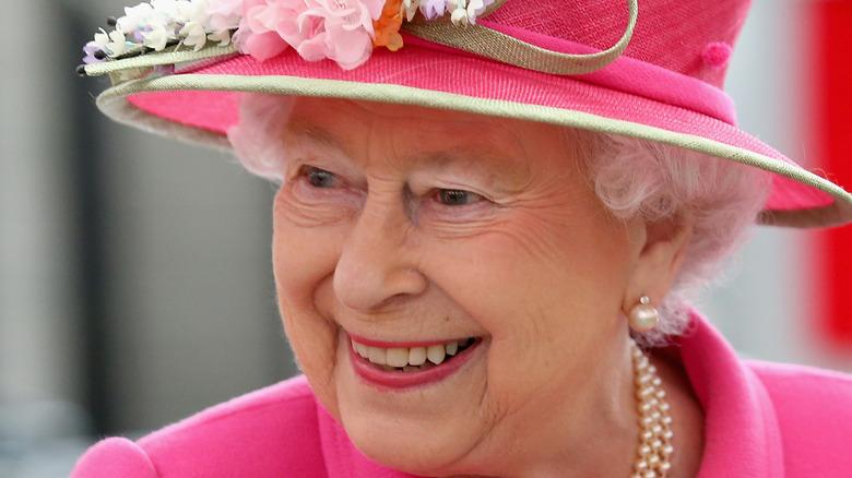 Queen Elizabeth II smiling in pink