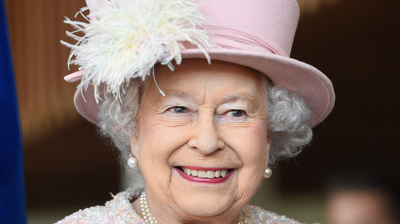 Queen Elizabeth smiling in a pink hat