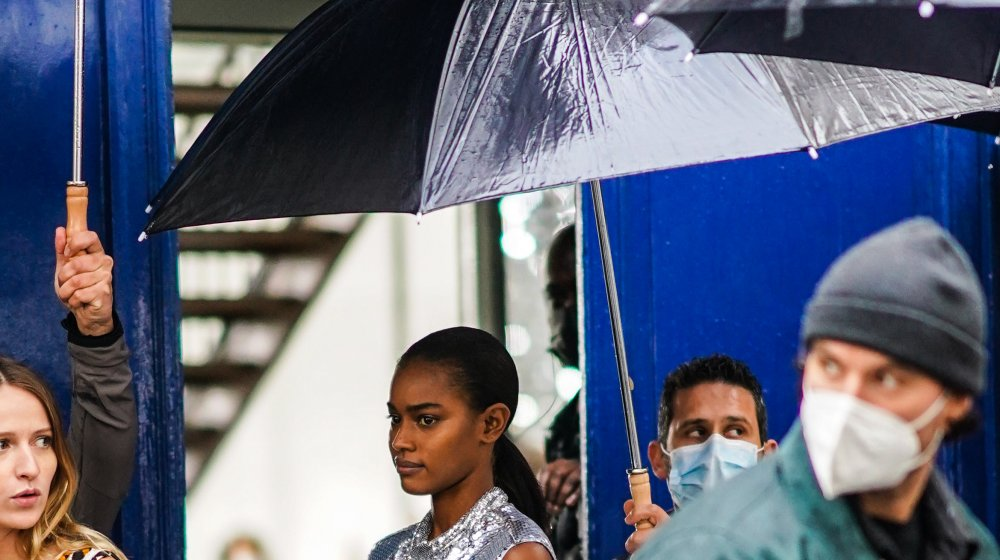 person with facemask on a rainy day
