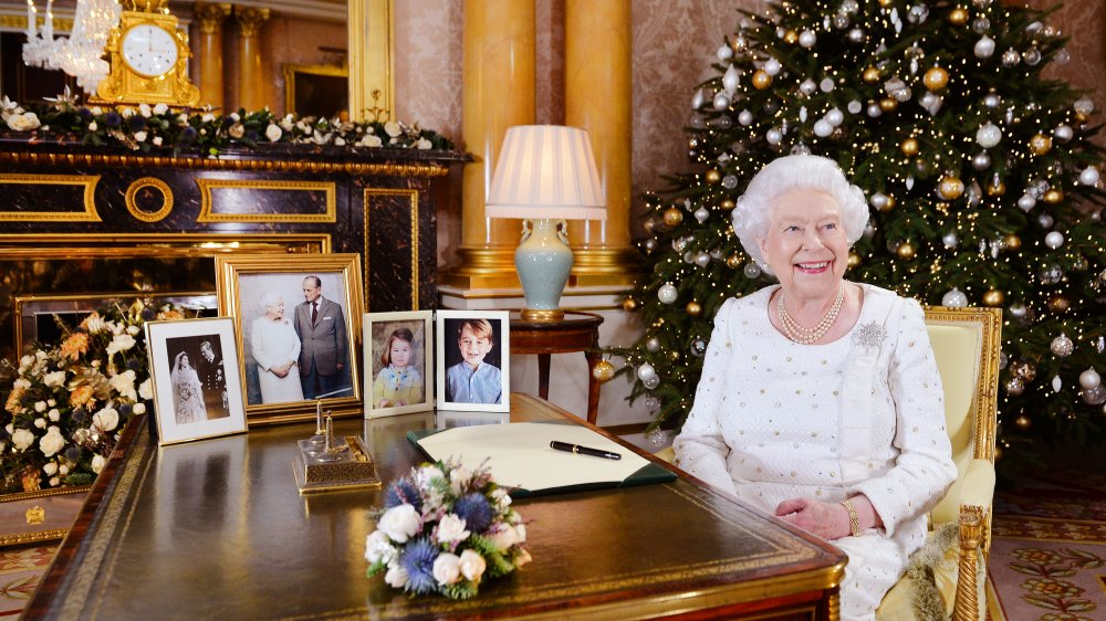 Queen Elizabeth sitting at a table by a Christmas tree