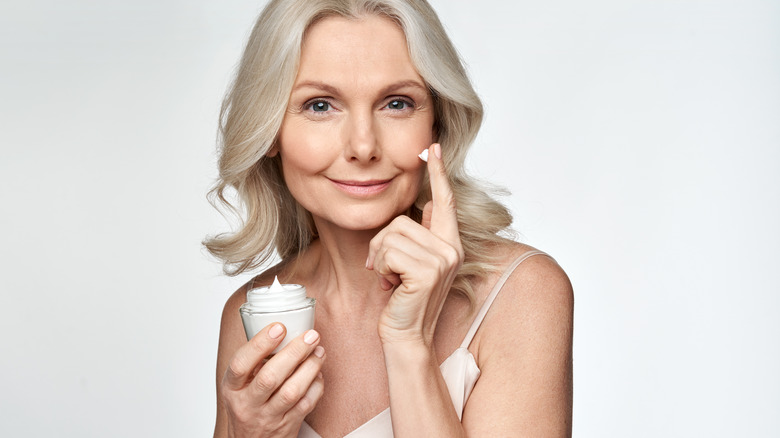 mature woman applying moisturizer to face