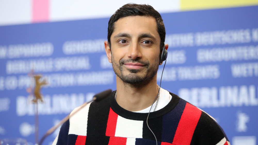 Riz Ahmed smiling with earpiece