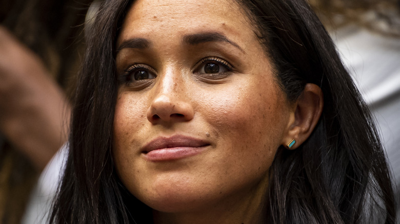 Meghan Markle looking on, smiling