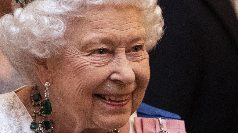 Queen Elizabeth smiling with emerald earrings