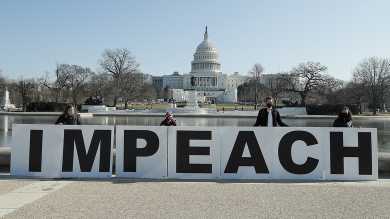 People outside the capitol with the impeachment sign