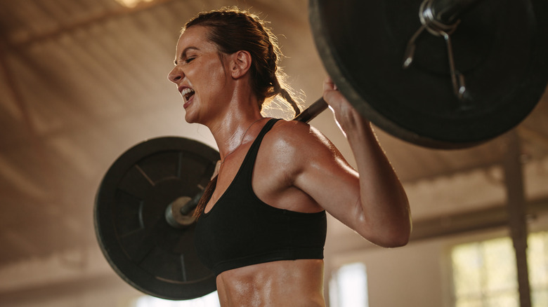 Woman lifting heavy weights at gym