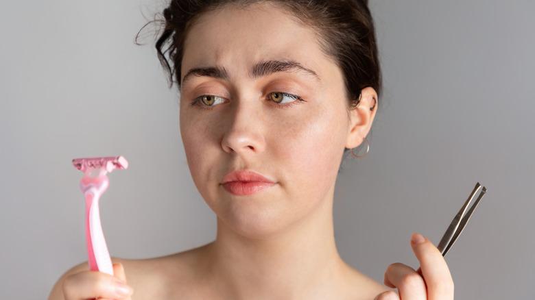 Woman with tweezers and razor