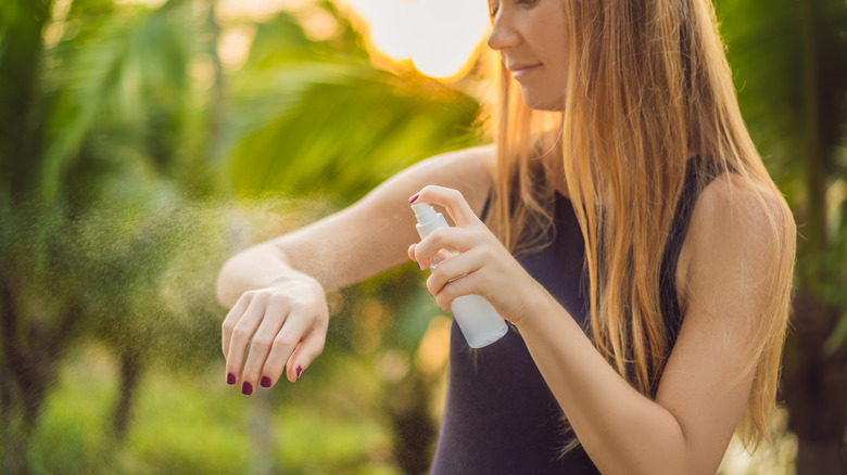 girl putting bug spray on arm outdoors