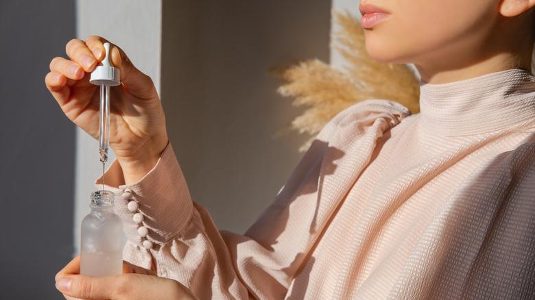 woman holding skin serum bottle