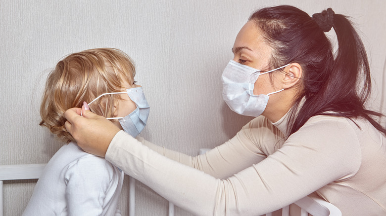 Mother putting mask on a child