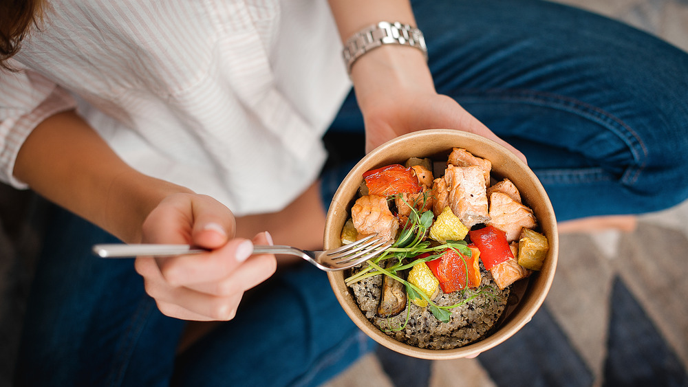 woman holding bowl of healthy food