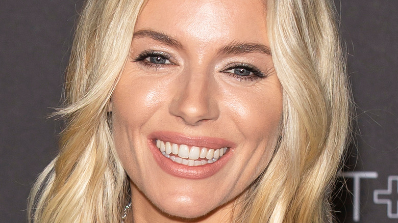 close up of actor Sienna Miller with a bold red lip