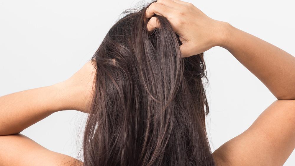 Woman scratching dry scalp hair
