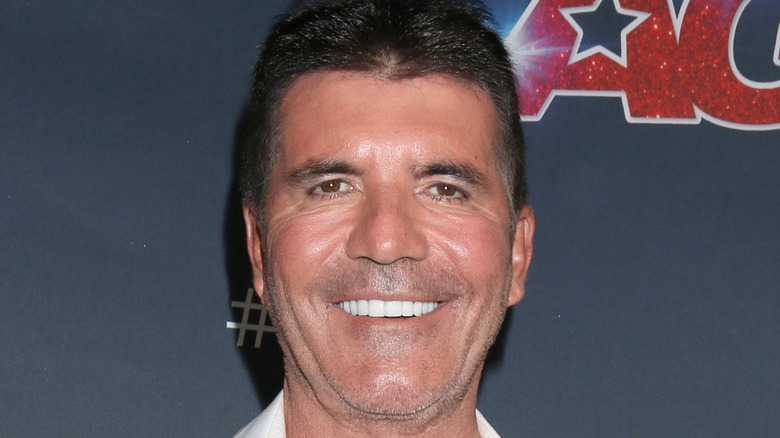 """Simon Cowell smiling on an """"America's Got Talent"""" red carpet"""