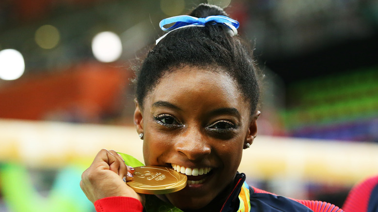 Simone Biles bites one of her gold medals