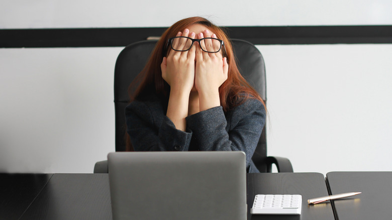 Woman covering her eyes at her desk